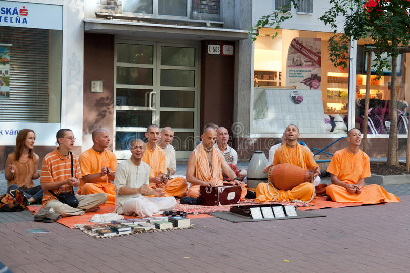 Members of Hare Krishna. Sit and sing on one of the central streets of Bratislava, Slovakia July 22, 2013 stock photography