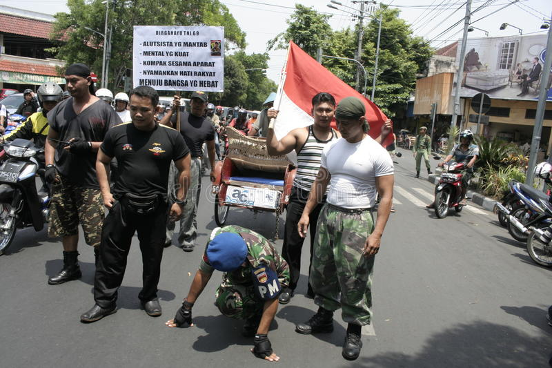 Members theatrical action Army Indonesia. Action Cpl Bagyo runs with squatting as a symbol of a strong army for the people of Indonesia stock photos