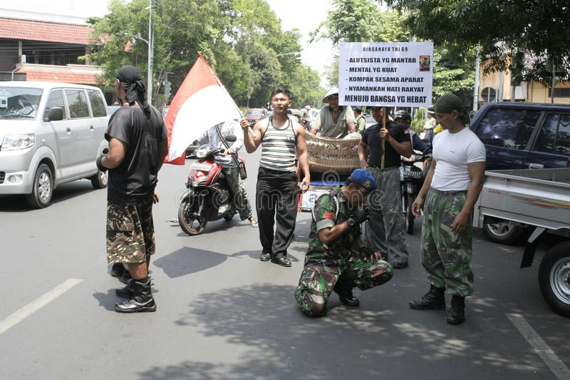 Members theatrical action Army Indonesia. Action Cpl Bagyo runs with squatting as a symbol of a strong army for the people of Indonesia stock image