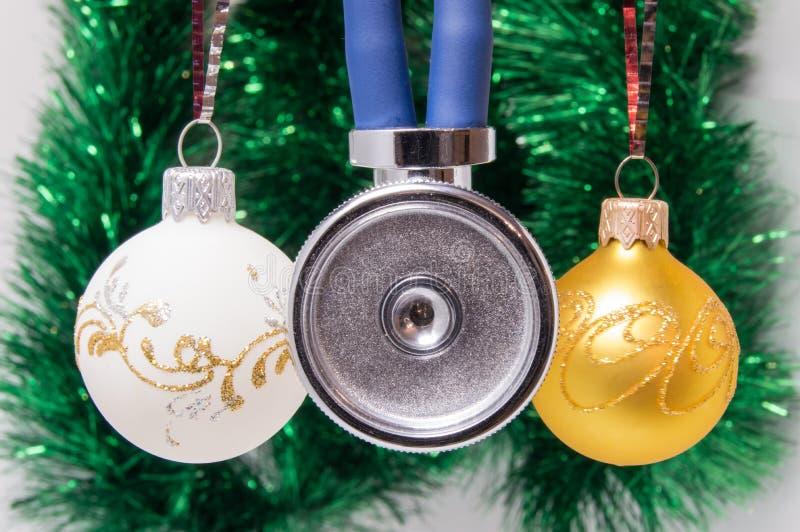Membrana médica del estetoscopio anterior con dos tubos rodeados por las bolas del árbol de navidad en fondo borroso con el adorn imagen de archivo libre de regalías
