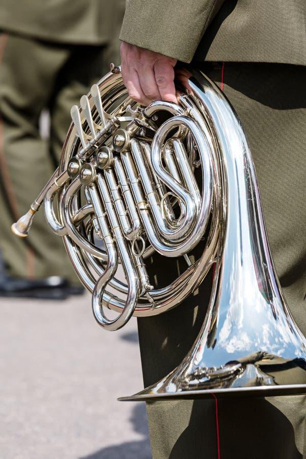 Membre d'un orchestre militaire tenant le klaxon dans sa main pendant l'o photographie stock