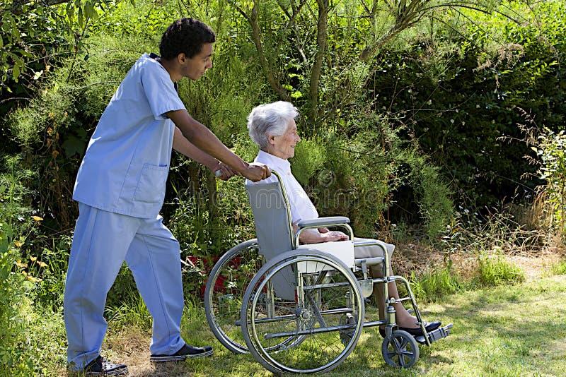 Membre du personnel d'hôpital poussant un patient supérieur heureux images libres de droits