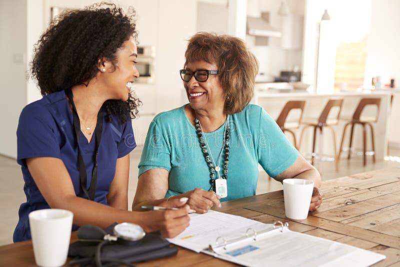 Membre du personnel soignant féminin s'asseyant à la table souriant avec une femme supérieure pendant une visite de soins à domic image stock