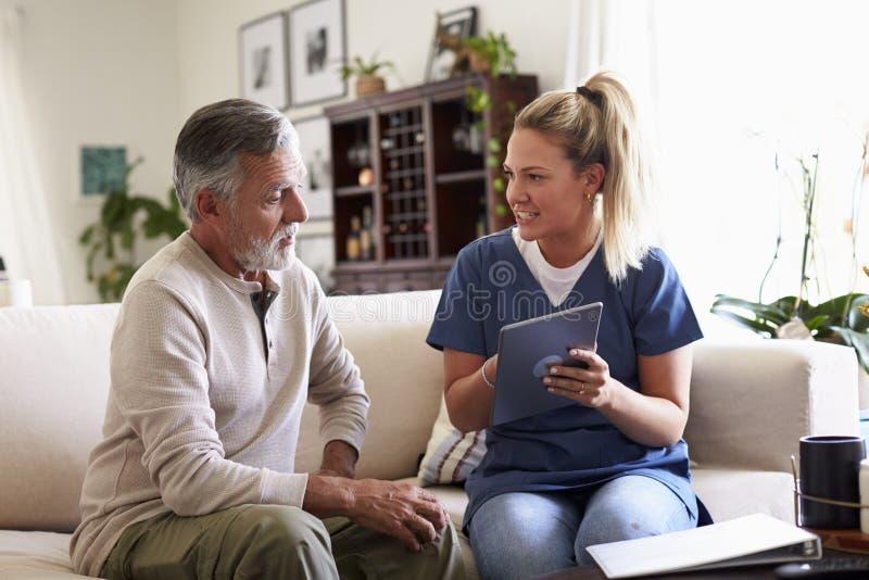 Membre du personnel soignant féminin s'asseyant avec un homme hispanique supérieur dans son salon pendant une visite à la maison photo stock