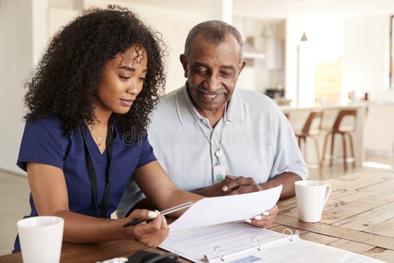 Membre du personnel soignant féminin vérifiant des résultats d'essai avec un homme supérieur pendant une visite de soins à domici photos stock