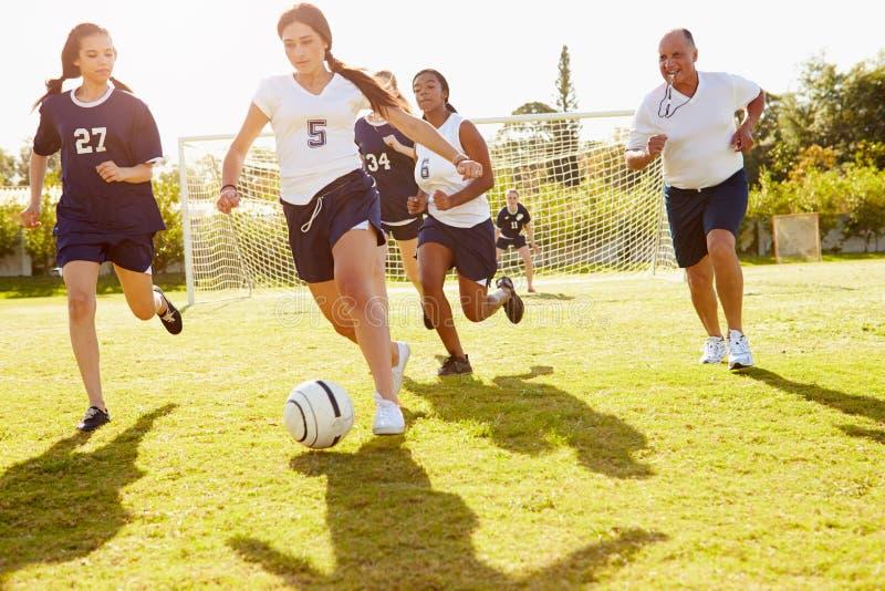 Membres du football femelle de lycée jouant le match image stock