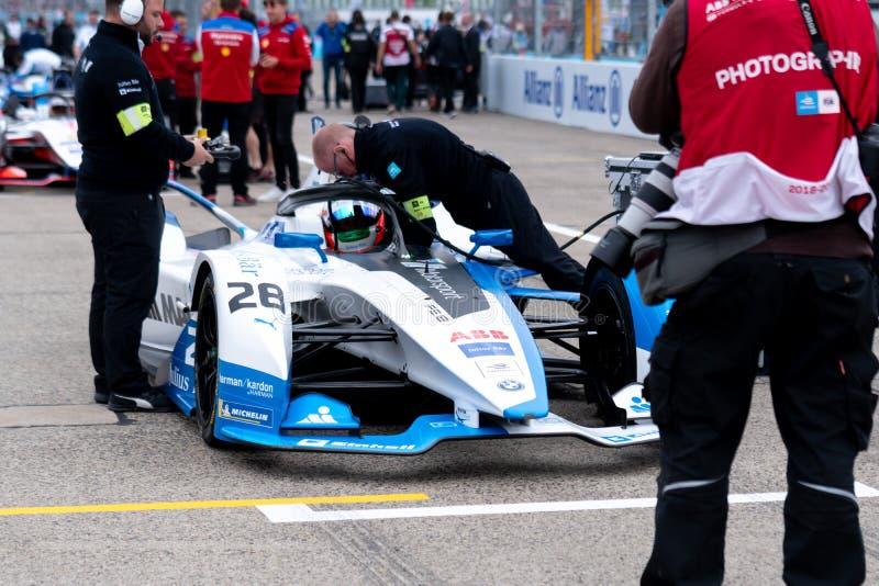 Membres du personnel de BMW vérifiant une voiture de course photographie stock