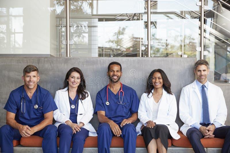 Membres du personnel soignant s'asseyant dans l'hôpital, longueur de trois-quarts photo libre de droits