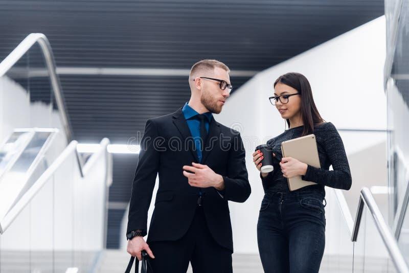 Membri del team sorridenti di affari che parlano durante la pausa caff?, il giovane uomo d'affari e la donna di affari aventi pia fotografie stock libere da diritti