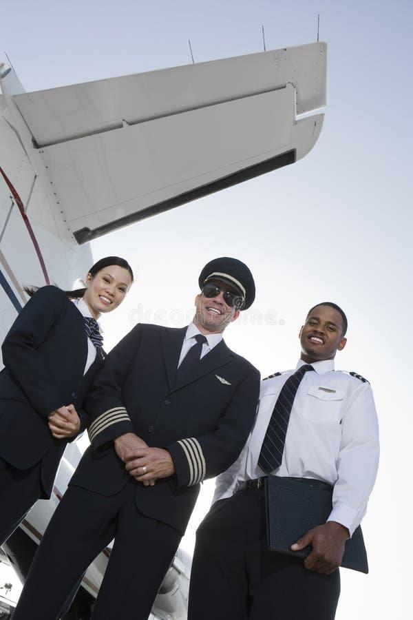Membri della squadra della cabina che stanno insieme all'aerodromo immagine stock libera da diritti