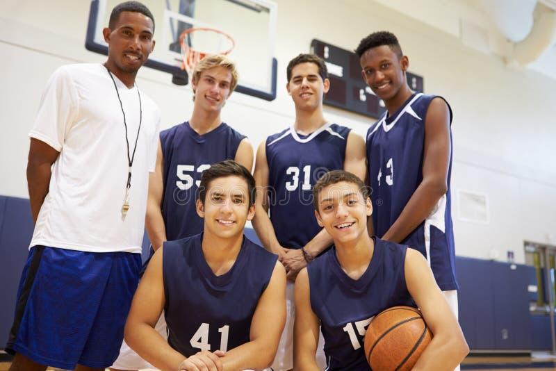 Membri di pallacanestro maschio Team With Coach della High School immagini stock