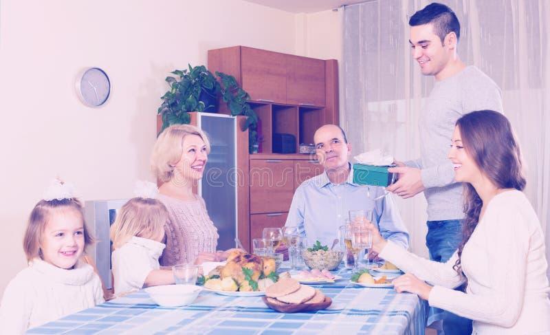 Membro della famiglia sorridente che riceve presente immagini stock