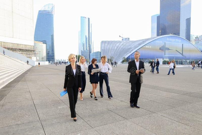 Membros da equipa financeiros que passam com tabuleta, casos e olhando fotografia de stock
