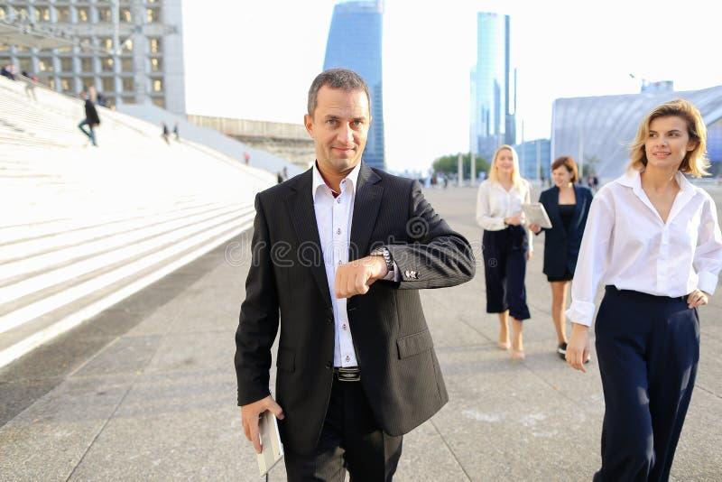 Membros da equipa financeiros que passam com tabuleta, casos e olhando imagens de stock