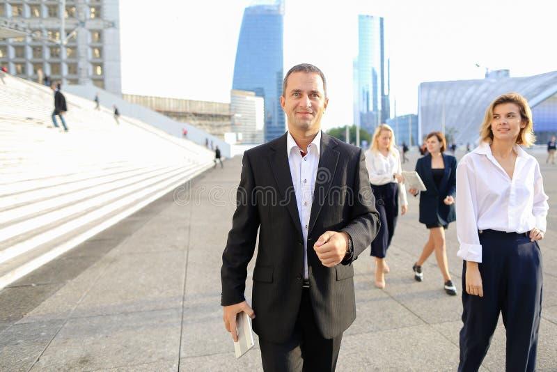 Membros da equipa financeiros que passam com tabuleta, casos e olhando fotografia de stock royalty free