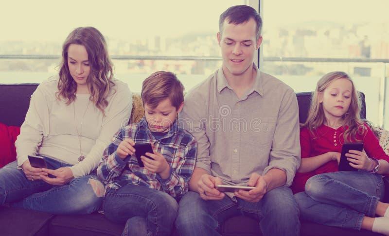 Membros da família alegres que passam o tempo que joga com smartphones fotos de stock royalty free