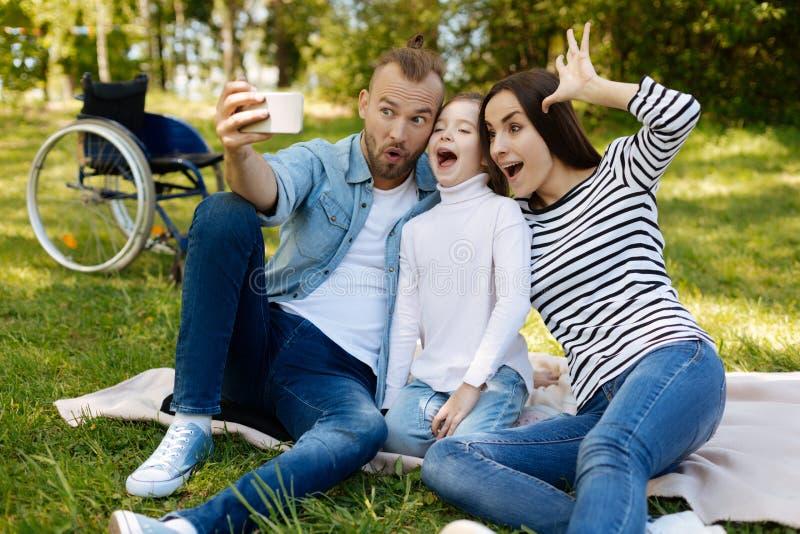 Membros da família engraçados ao fazer as caras fotografia de stock
