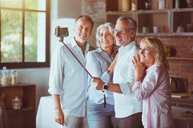 Membros da família envelhecidos positivo que fazem selfies imagens de stock