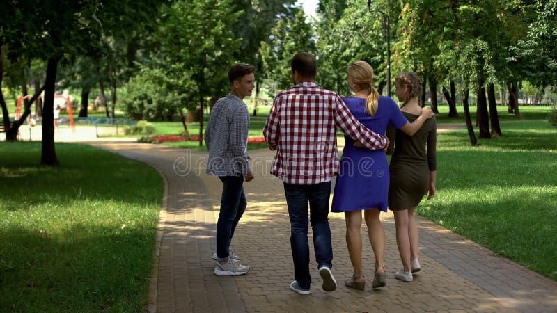 Membros da família satisfeitos que andam no parque, apreciando o fim de semana perfeito junto imagens de stock royalty free