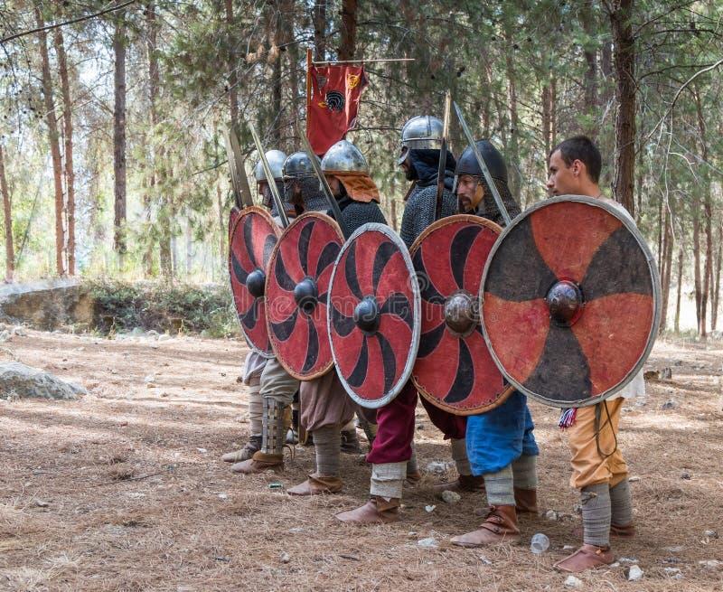 Membros da reconstrução anual da vida dos Viquingues - o ` de Viking Village do ` demonstra a formação de combate na floresta pró fotos de stock