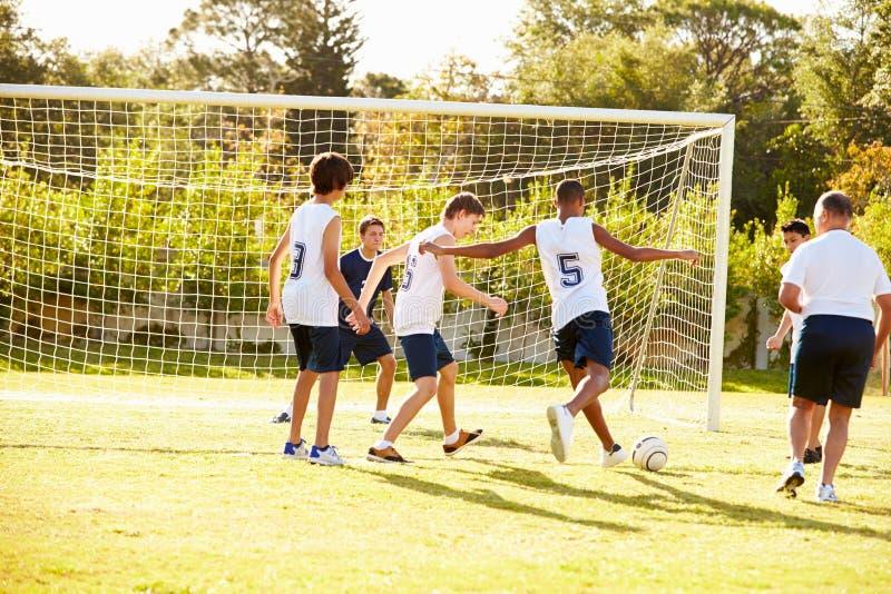Membros do futebol masculino da High School que joga o fósforo imagens de stock royalty free