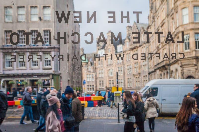 Membros do público na parte da milha real histórica de Edimburgo que é alinhado com lojas, barras e restaurantes imagem de stock