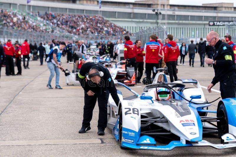 Membros do pessoal do Bmw que verificam um carro de corridas fotografia de stock royalty free