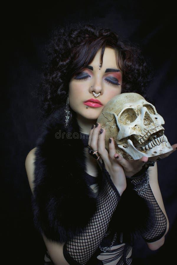 Memento mori. Pretty gothic girl with skull over dark background stock photography