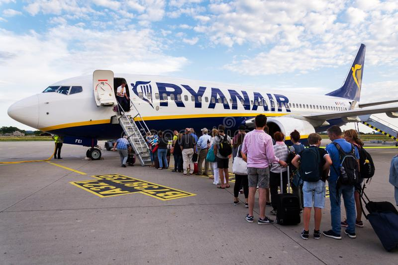 People boarding Ryanair Irish low-cost airline plane Boeing 737 with cloudy sky background. MEMMINGEN, GERMANY - JULY 6 2019: People boarding Ryanair Irish low stock photos