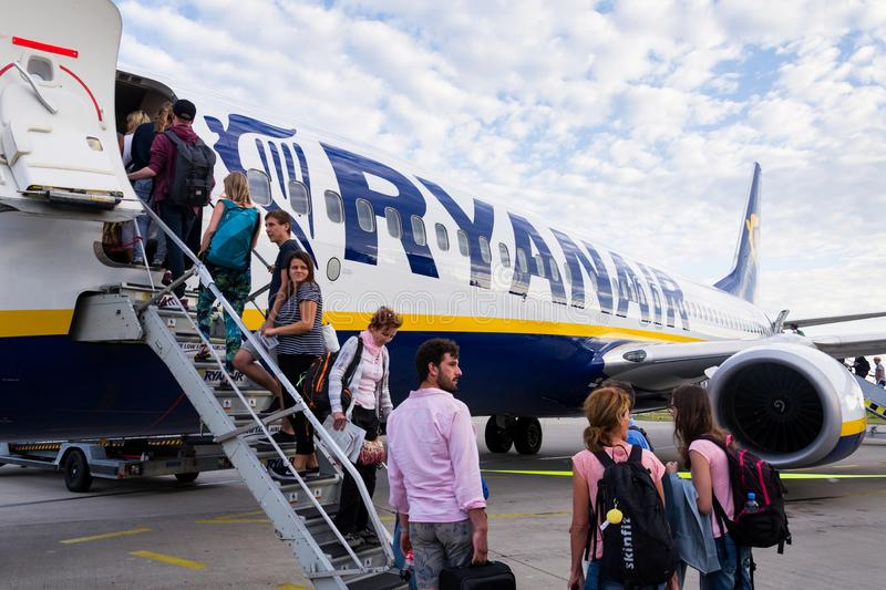 People boarding Ryanair Irish low-cost airline plane Boeing 737 with cloudy sky background. MEMMINGEN, GERMANY - JULY 6 2019: People boarding Ryanair Irish low stock images