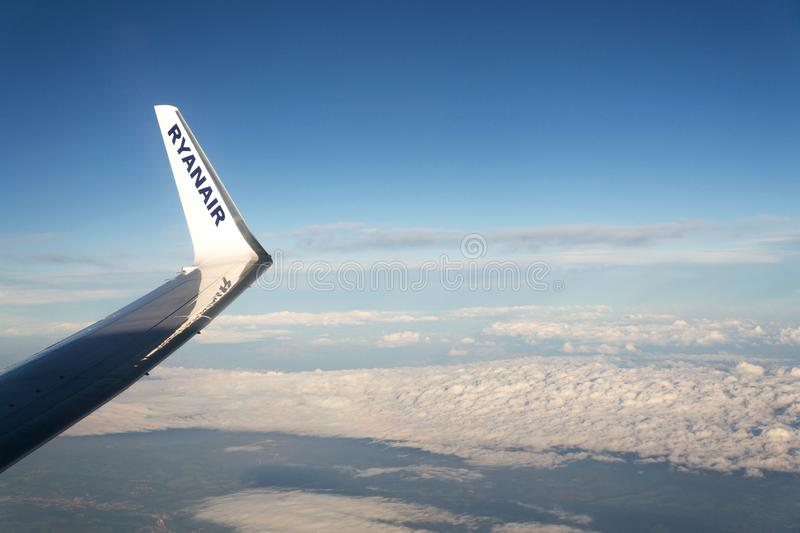 Ryanair Irish low-cost airline Boeing 737 wing during flight with cloudy sky background. MEMMINGEN, GERMANY - JULY 6 2019: Ryanair Irish low-cost airline Boeing stock image