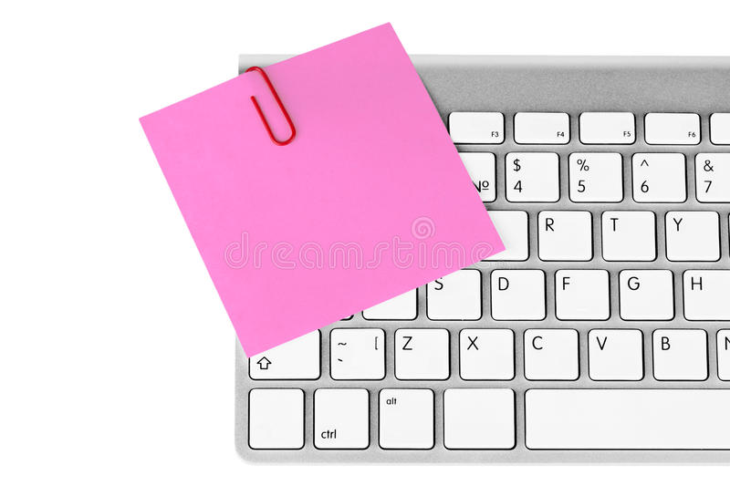 Memo and aluminum keyboard. Red memo and paper clip on aluminum keyboard on the white background royalty free stock photography