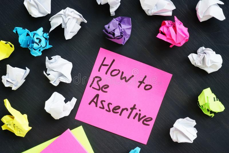 Memo with sign How to be Assertive. Memo stick with sign How to be Assertive stock images