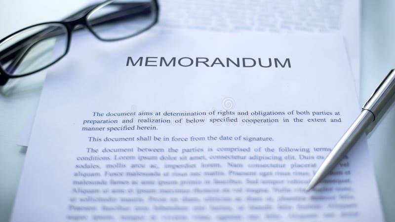 Memorándum que miente en la tabla, la pluma y las lentes en el documento oficial, negocio foto de archivo libre de regalías