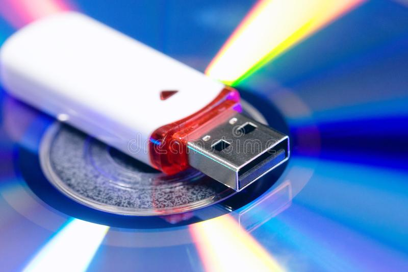 Memoria USB en fondo del disco del Cd Nueva y vieja tecnología equipo para almacenar la información verde rosado azul y amarillo  fotografía de archivo libre de regalías