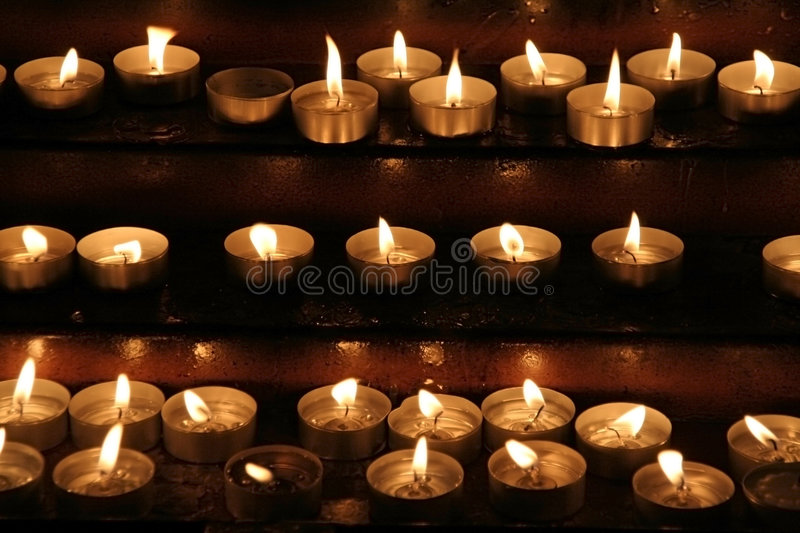 Memorial candles. Prayer candles aka offering, votive or memorial candles lit in a dark church royalty free stock photos