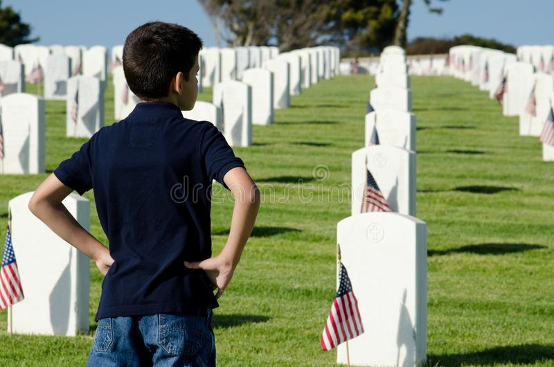 Memorial Day. A boy looking over the grave sites on Memorial Day at the National Cemtery in San Diego,CA stock photo