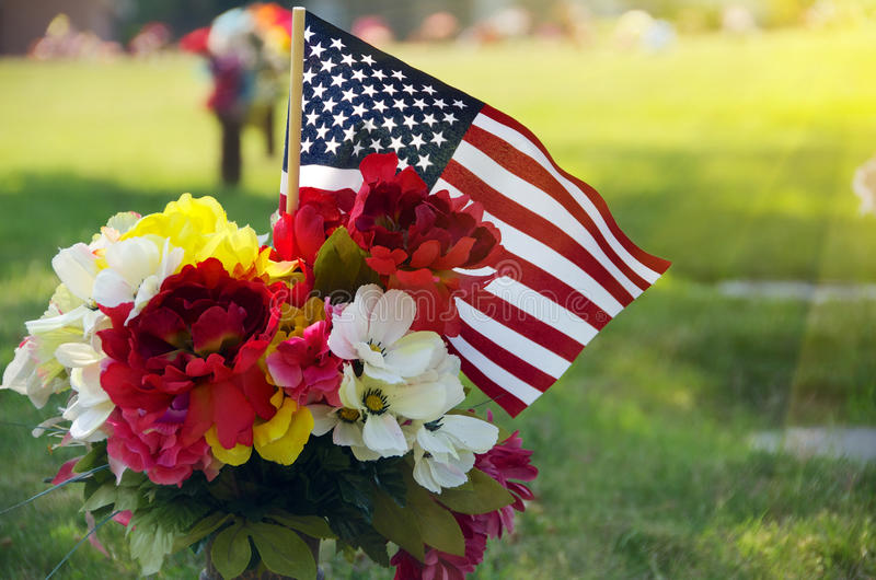 Memorial Day Flowers American Flag. Memorial Day Flowers with an American Flag placed on a American Veterans Memorial Grave stock photos