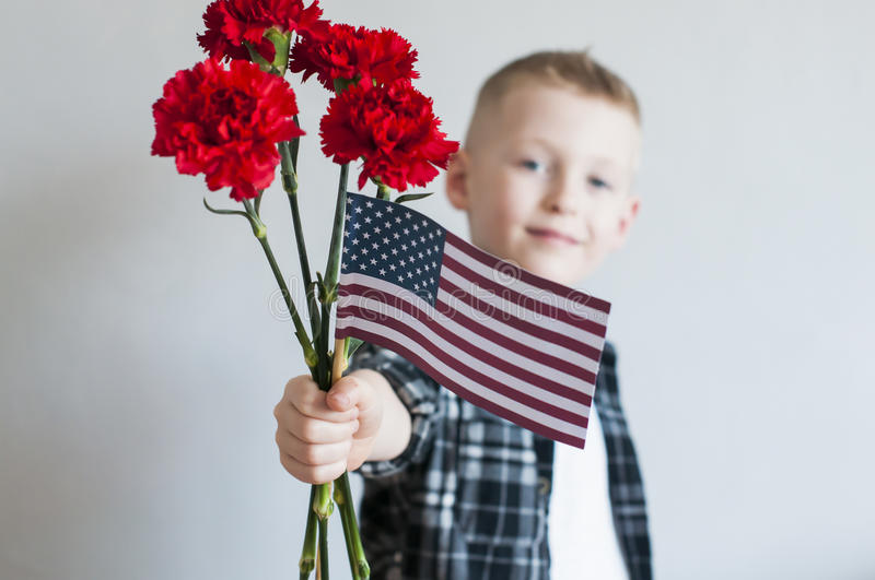 Memorial day with flowers and American flag. Proud cheerful boy celebrates Memorial day with flowers and American flag royalty free stock images