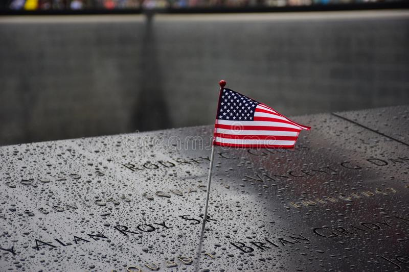Memorial at Ground Zero Manhattan for September 11 Terrorist Attack with an American Flag Standing near the Names of Victims Engra. Ved royalty free stock photos