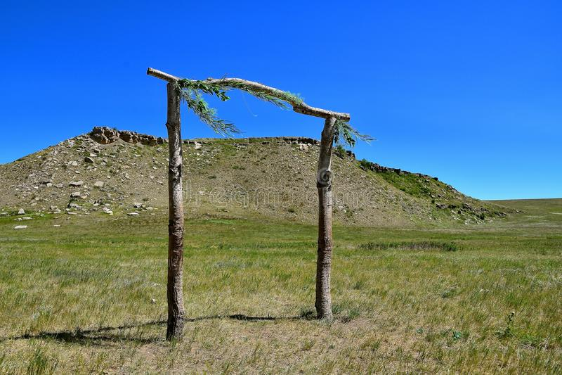 Memorial honoring Native Americans. Decorated poles in Standing Rock Reservation in front of a huge butte honoring Native Americans stock images