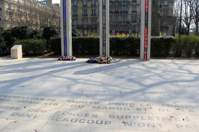 Memorial outside The Eiffel Tower, with flowers placed beneath tall columns,Paris,France,2016 stock photos