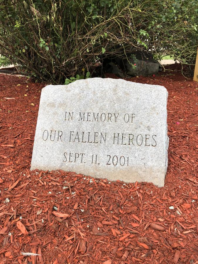 911 memorial stone marker. 911 memorial marker in a garden or other field on the ground with wood chips. Stone rock sign of remembrance and respect for the royalty free stock images