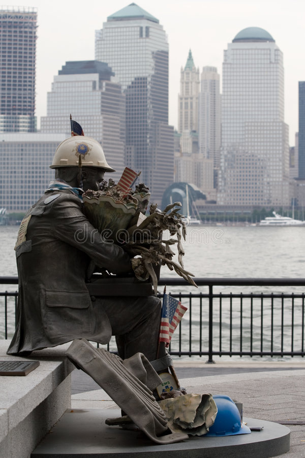 Memorial to 911 victims. A small statue commemorating victims of the 911 attack with a city skyline in the background stock photo