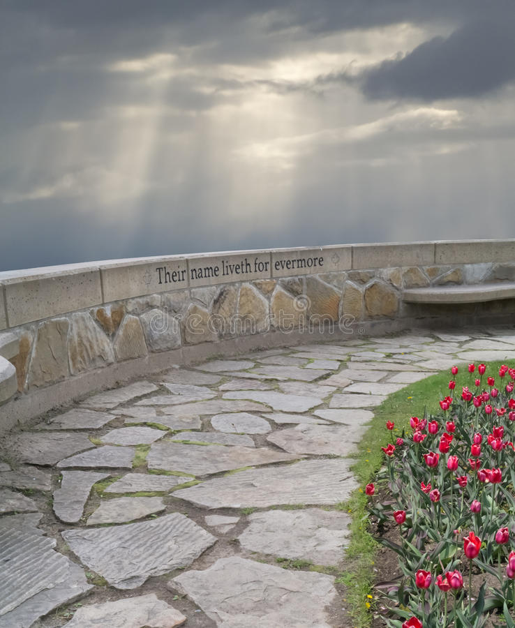 Memorial wall on path to remember those lost. A memorial wall on a flag stone path with tulip garden and bench with the words Their name liveth for evermore stock photos