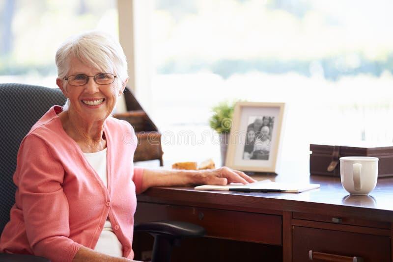 Memorias mayores de la escritura de la mujer en libro en el escritorio imagen de archivo