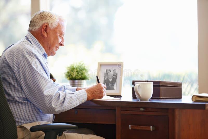 Memorie di scrittura dell'uomo senior in libro che si siede allo scrittorio immagini stock