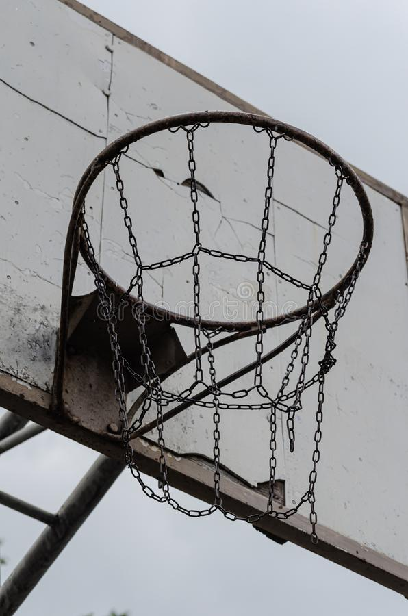 Basketball backboard with basket on the old playground. Shooting from the bottom up against the cloudy sky. royalty free stock image