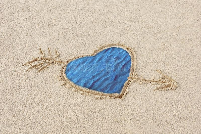 Heart drawn on the sand pierced by an arrow royalty free illustration