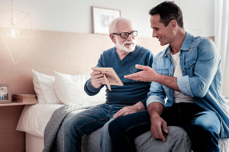 Delighted aged man holding a photo. Always in memory. Delighted nice aged men holding a photo and smiling while talking to his grandson royalty free stock photography